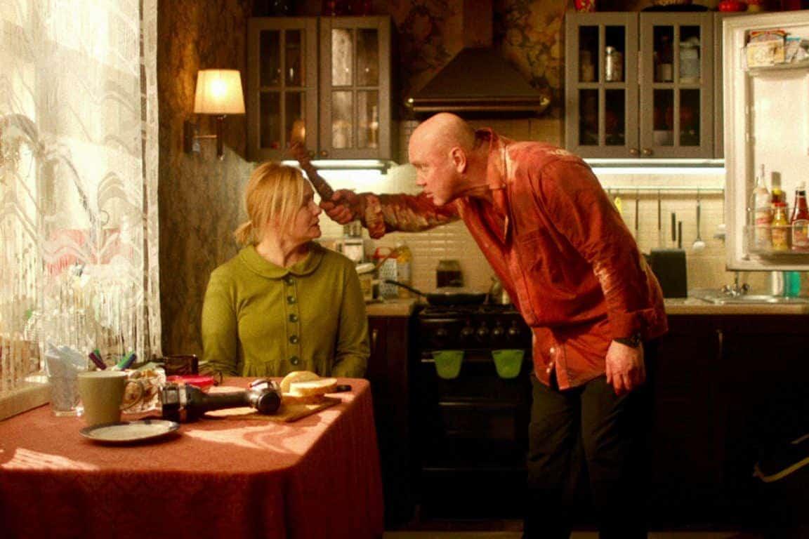 Tasha (Elena Shevhenko) and Andrey (Vitaliy Khaev) in their kitchen as Andrey eats meat and yells.