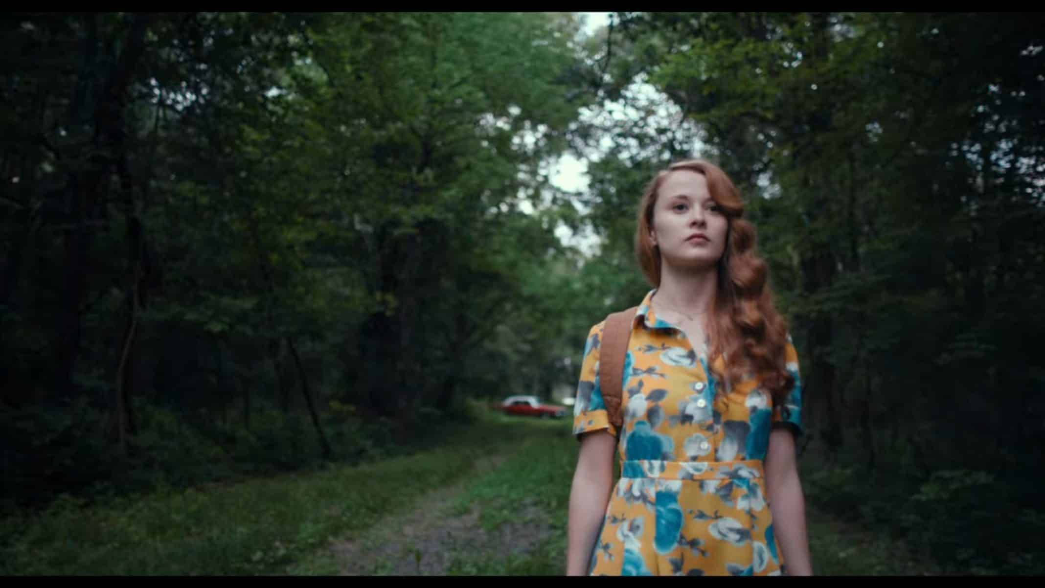 Bess (Shannon Tarbet) walking in the woods.