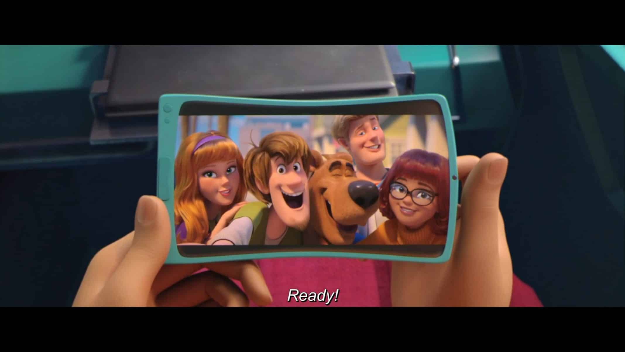 Daphne (Amanda Seyfried), Shaggy (Will Forte), Scooby (Frank Wlker), Fred (Zac Efron), and Velma (Gina Rodriguez) taking a picture together.