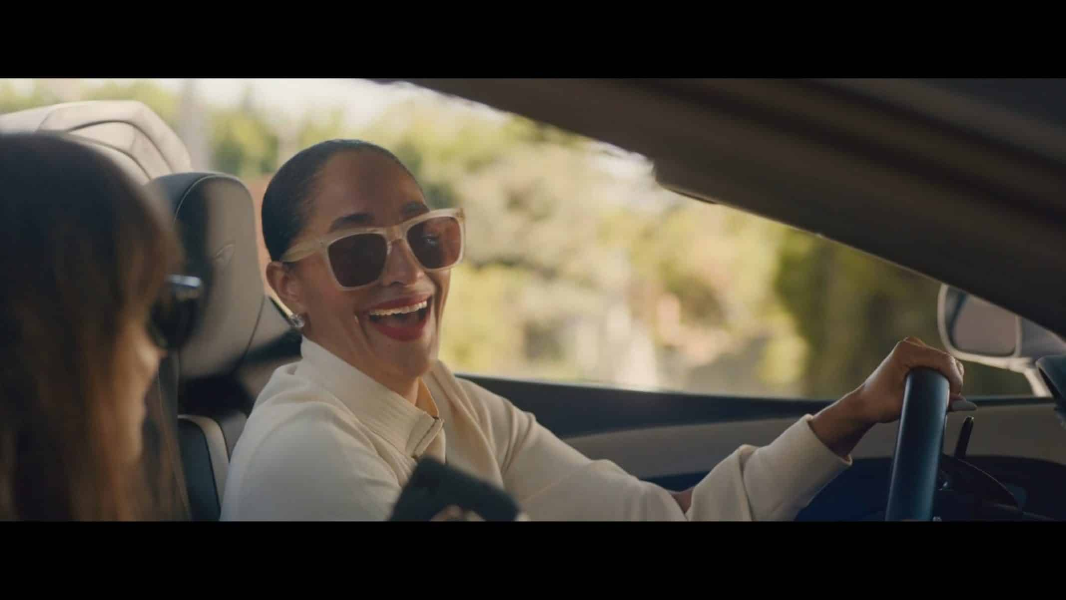 Grace (Tracee Ellis Ross) smiling and driving her car.