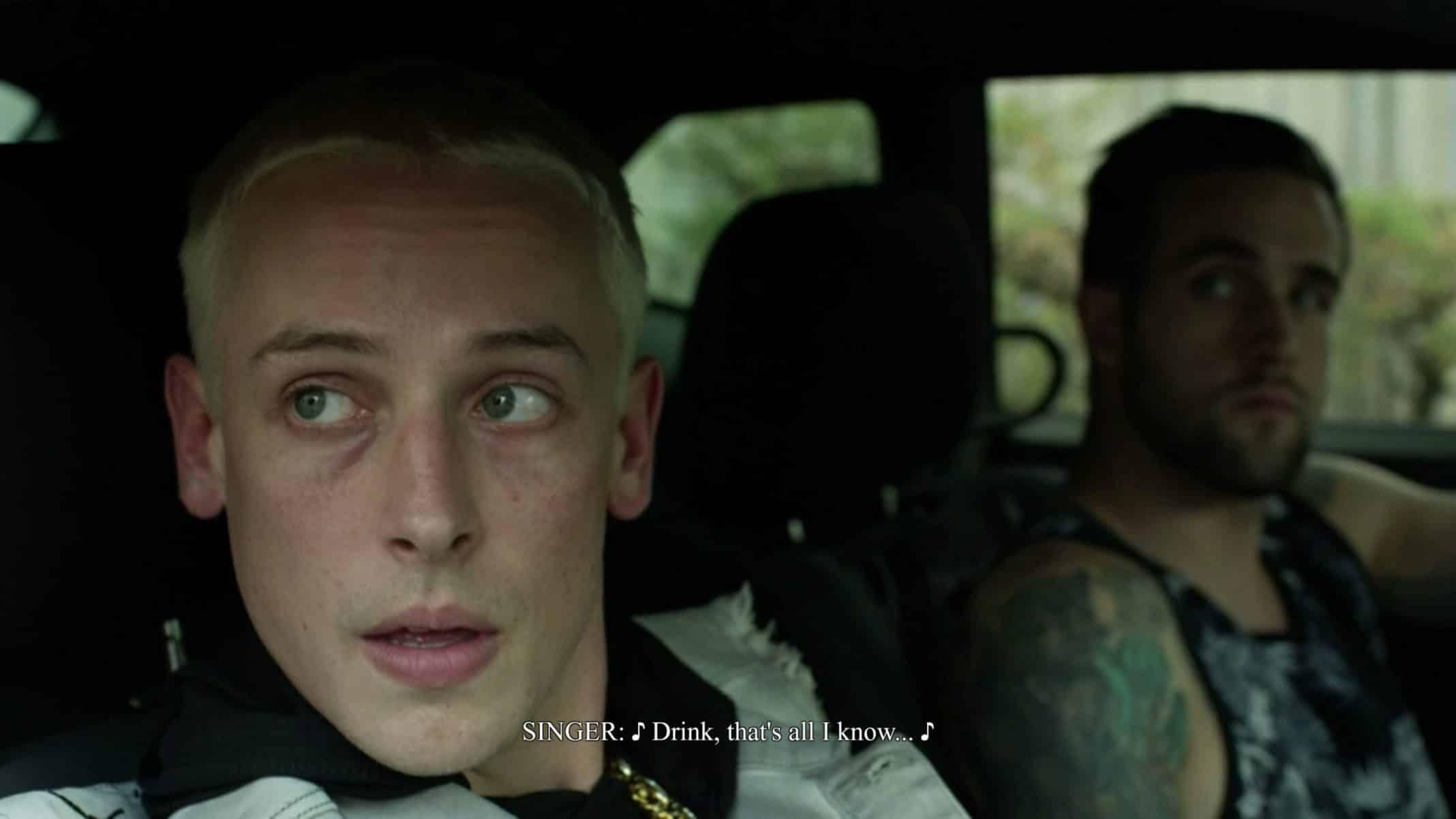 Kizzle (Edumund Donovan) in a car talking to Junior.