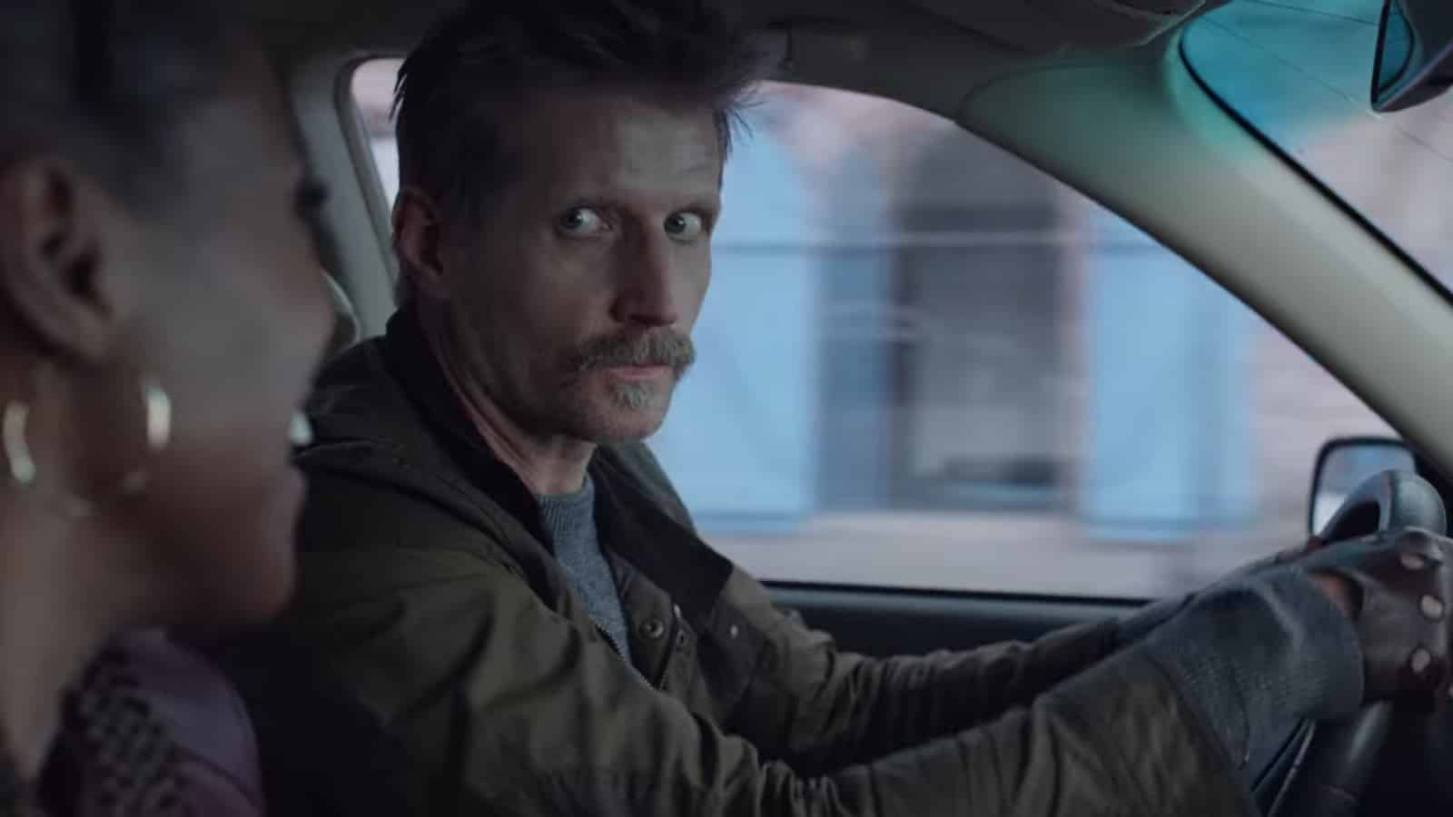 Mustache (Paul Sparks) looking over at Leilani.