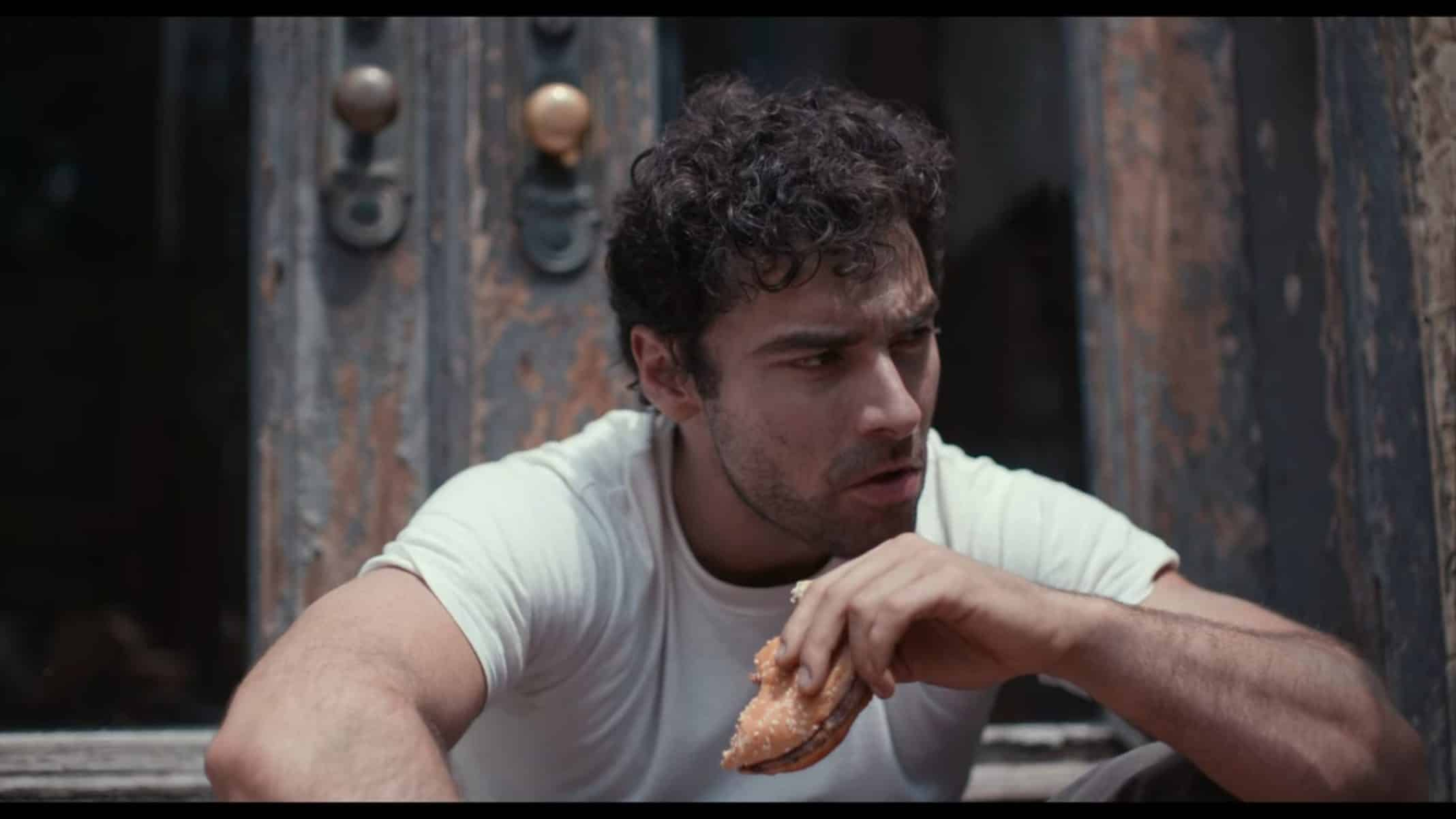 Russell (Aidan Turner) eating a burger.