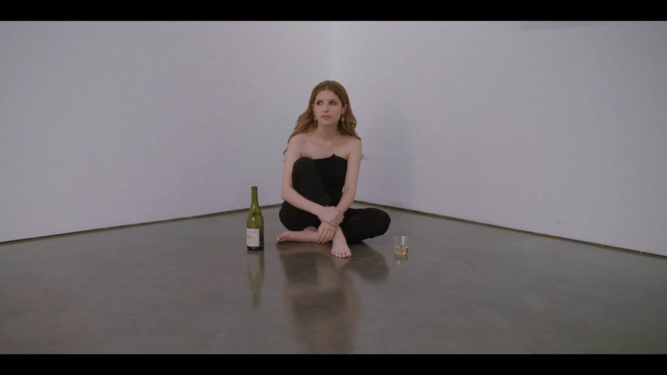 Darby sitting on the floor, barefoot, after a successful art showing.