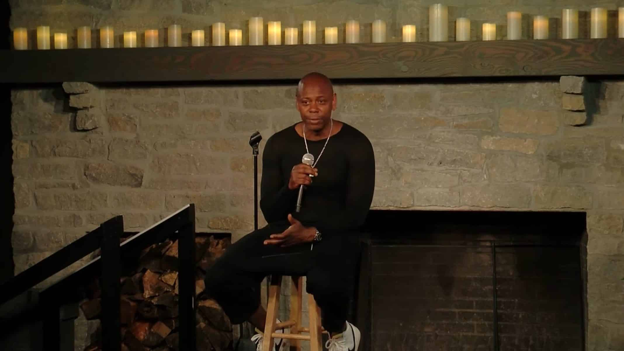 Dave Chappelle sitting on a stool, talking to an audience.