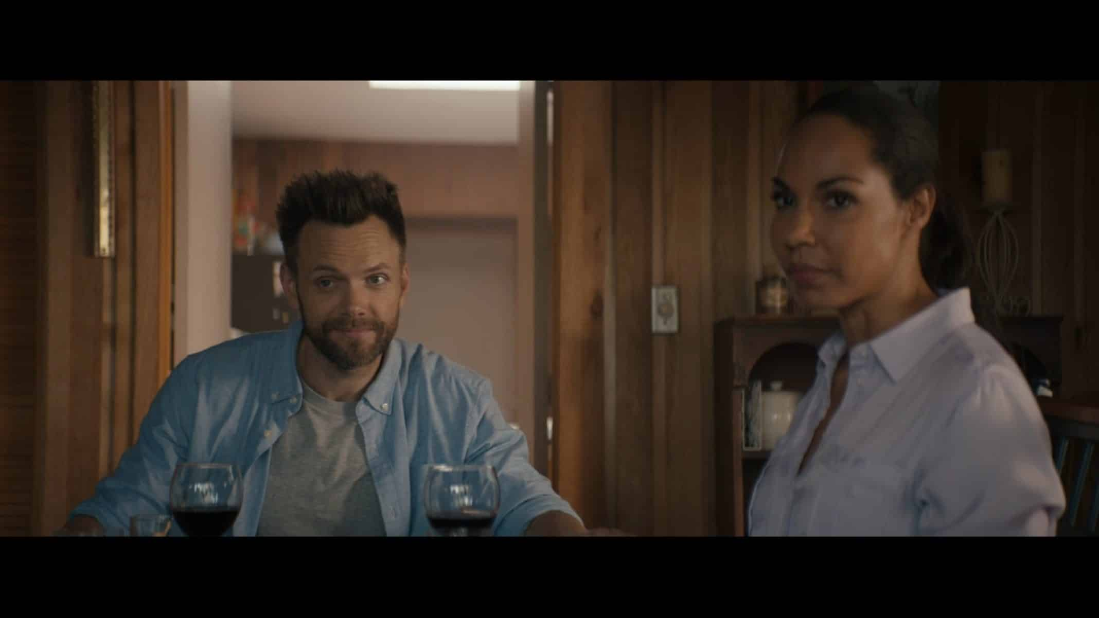 Jeff (Joel McHale) and Kayla (Amanda Brugel) looking towards Becky while they have dinner.