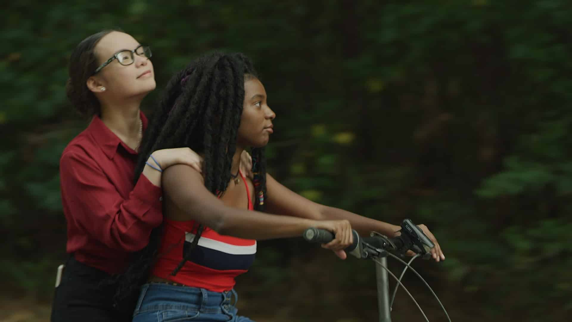 Gabby (Gabriella Pastore) on the back of Lulu's (Ja'ness Tate) bike.
