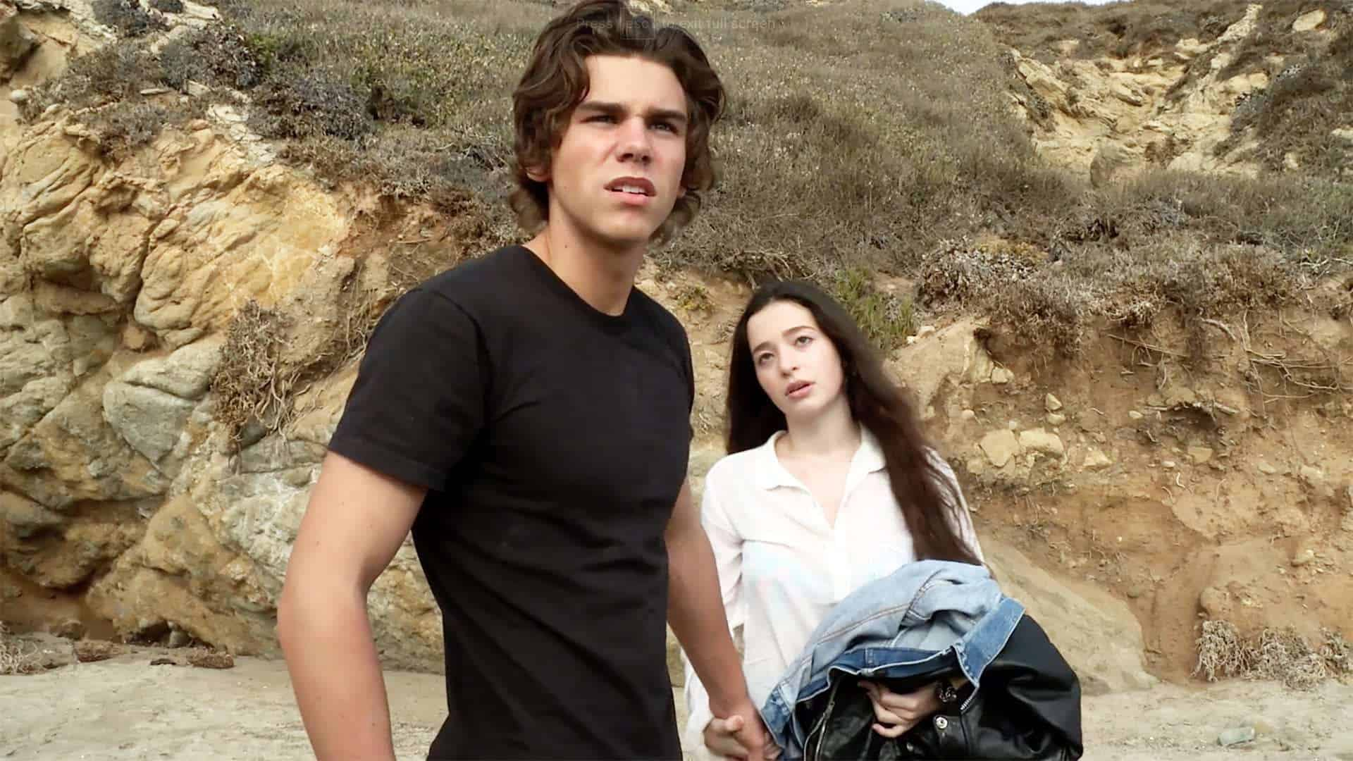 Brett (Sean H. Scully) and Liza (Mikey Madison) on a beach, being harassed.