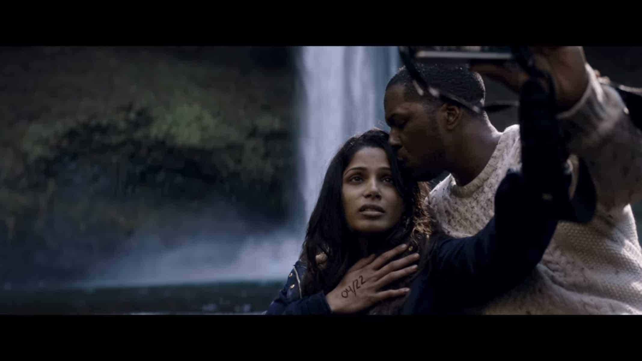 Eva (Frieda Pinto) and Will (Leslie Odom Jr.) in front of a waterfall.