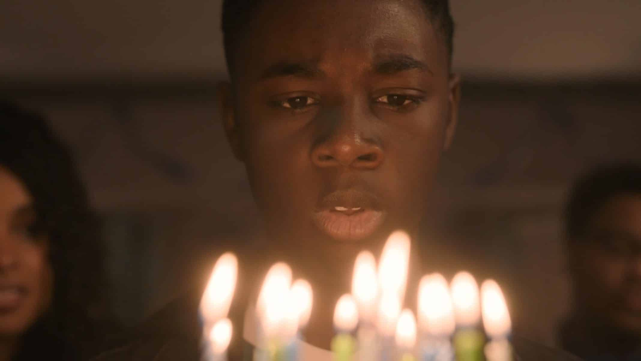 Kevin (Alex R. Hibbert) blowing out his birthday candles