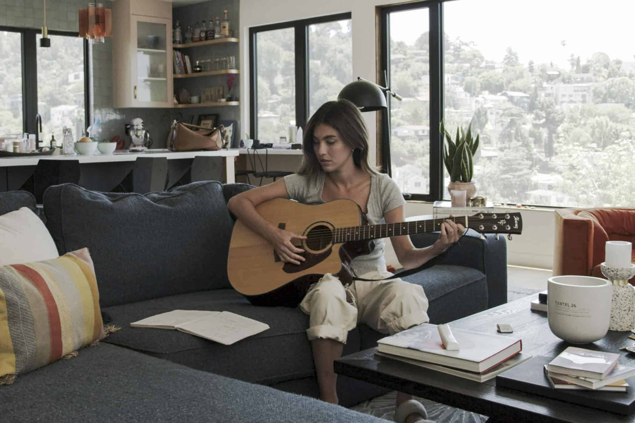 Elle (Rainey Qualley) playing her guitar.