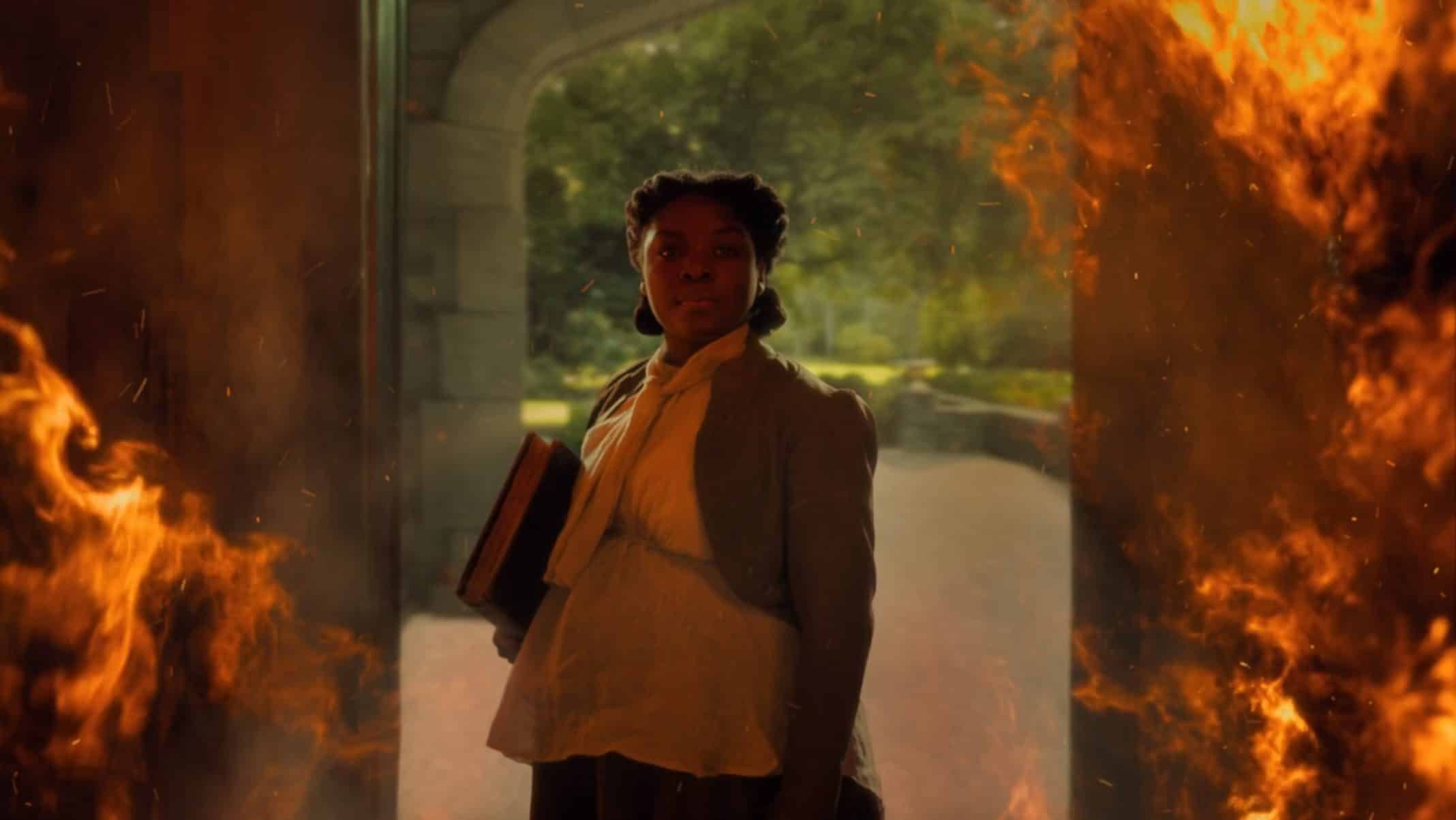 Hannah (Joaquina Kalukango) in a doorway, surrounded by fire.