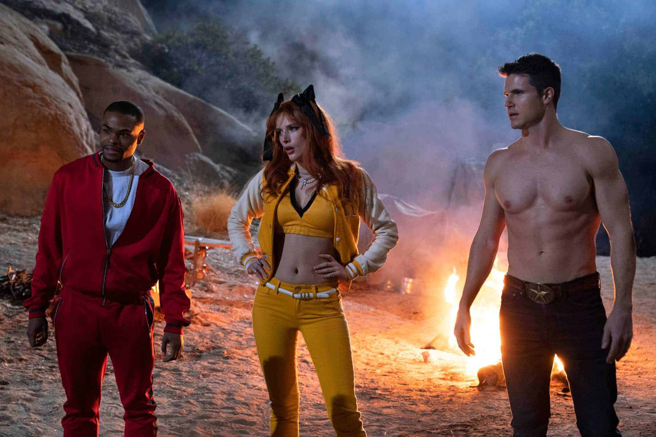 ANDREW BACHELOR as JOHN, BELLA THORNE as ALLISON and ROBBIE AMELL as MAX standing in front of a fire.