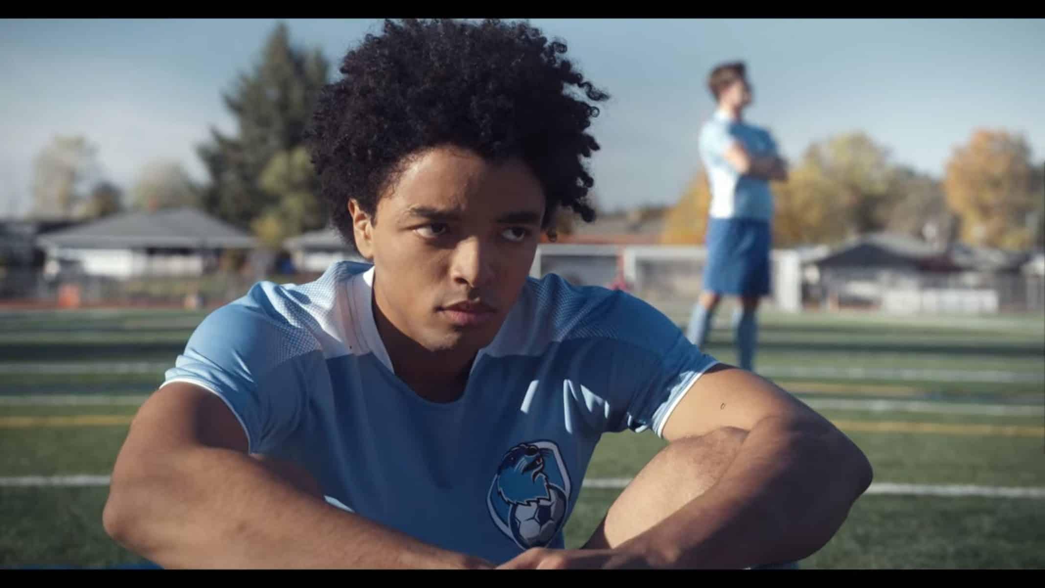 Noah (Odiseas Georgiadis) sitting on the soccer field, upset.