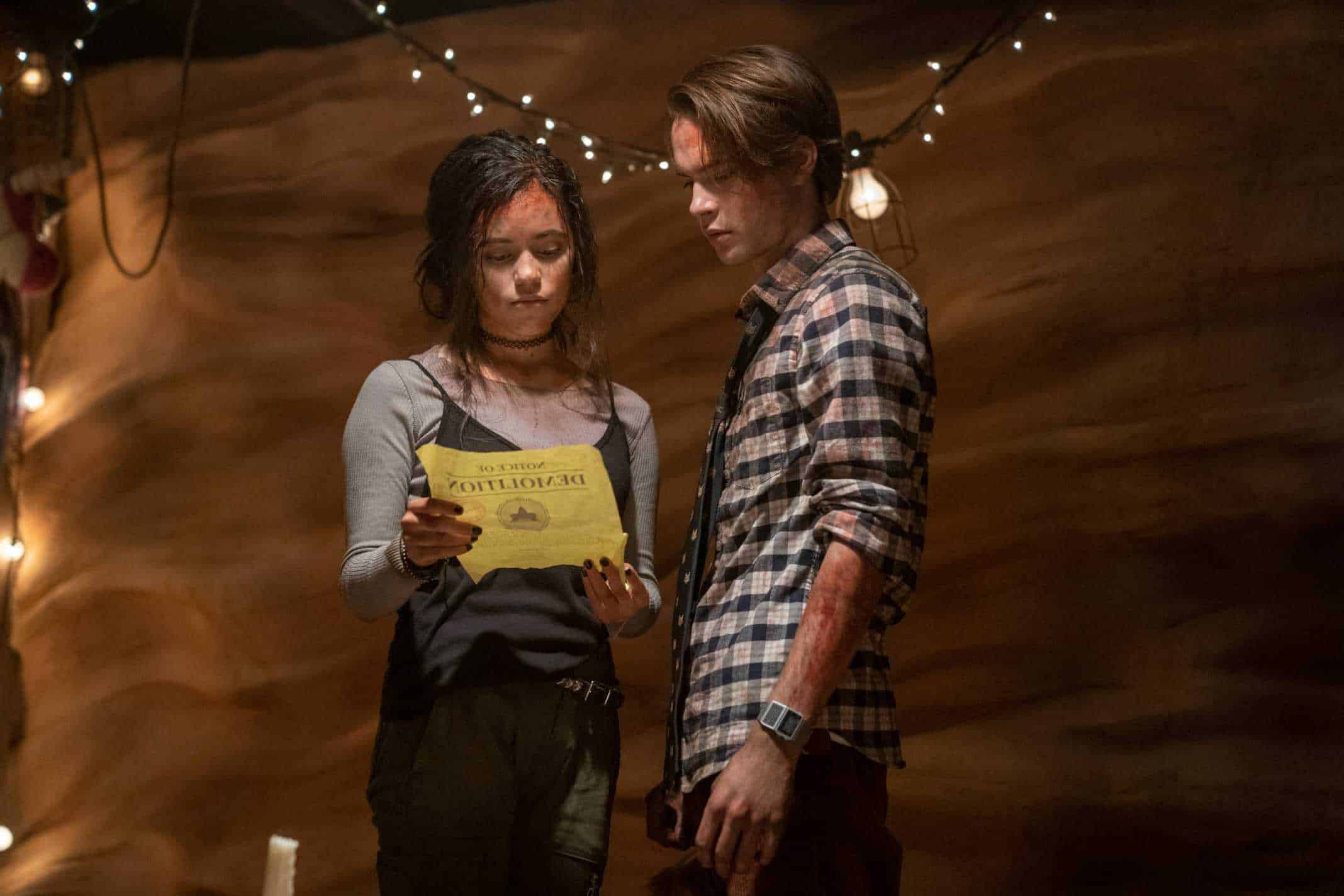 JENNA ORTEGA as PHOEBE and JUDAH LEWIS as COLE looking at a piece of paper, seemingly with blood on them.