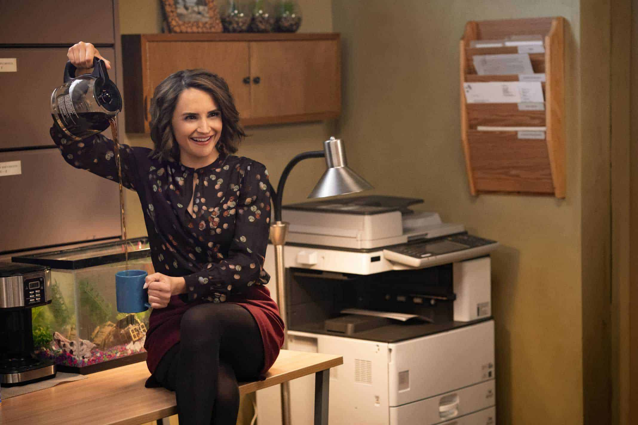 Susan (Rachel Leigh Cook) on a table, pouring coffee.