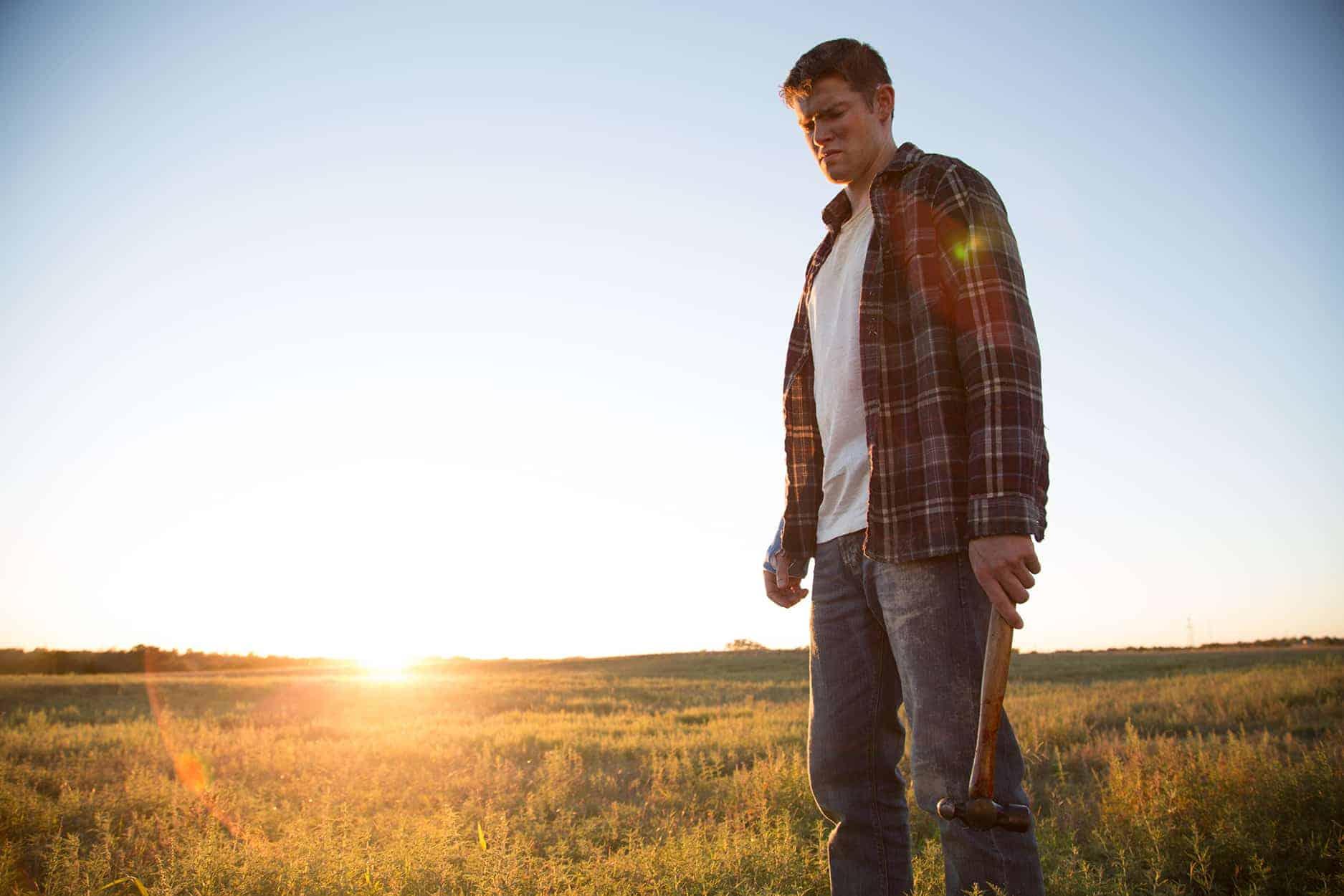 Brandon (Alex MacNicoll) standing outside in the Texas sun.