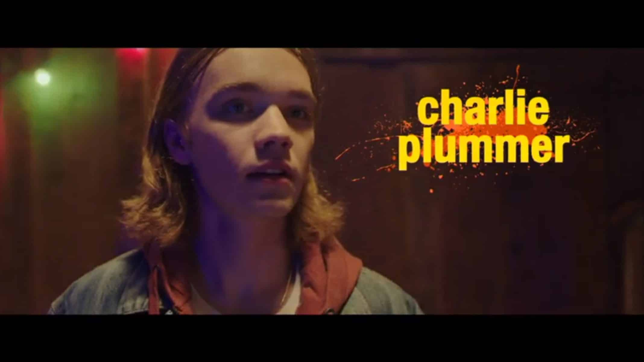 Dylan (Charlie Plummer)  with his long locks on his shoulders, stunned by something.