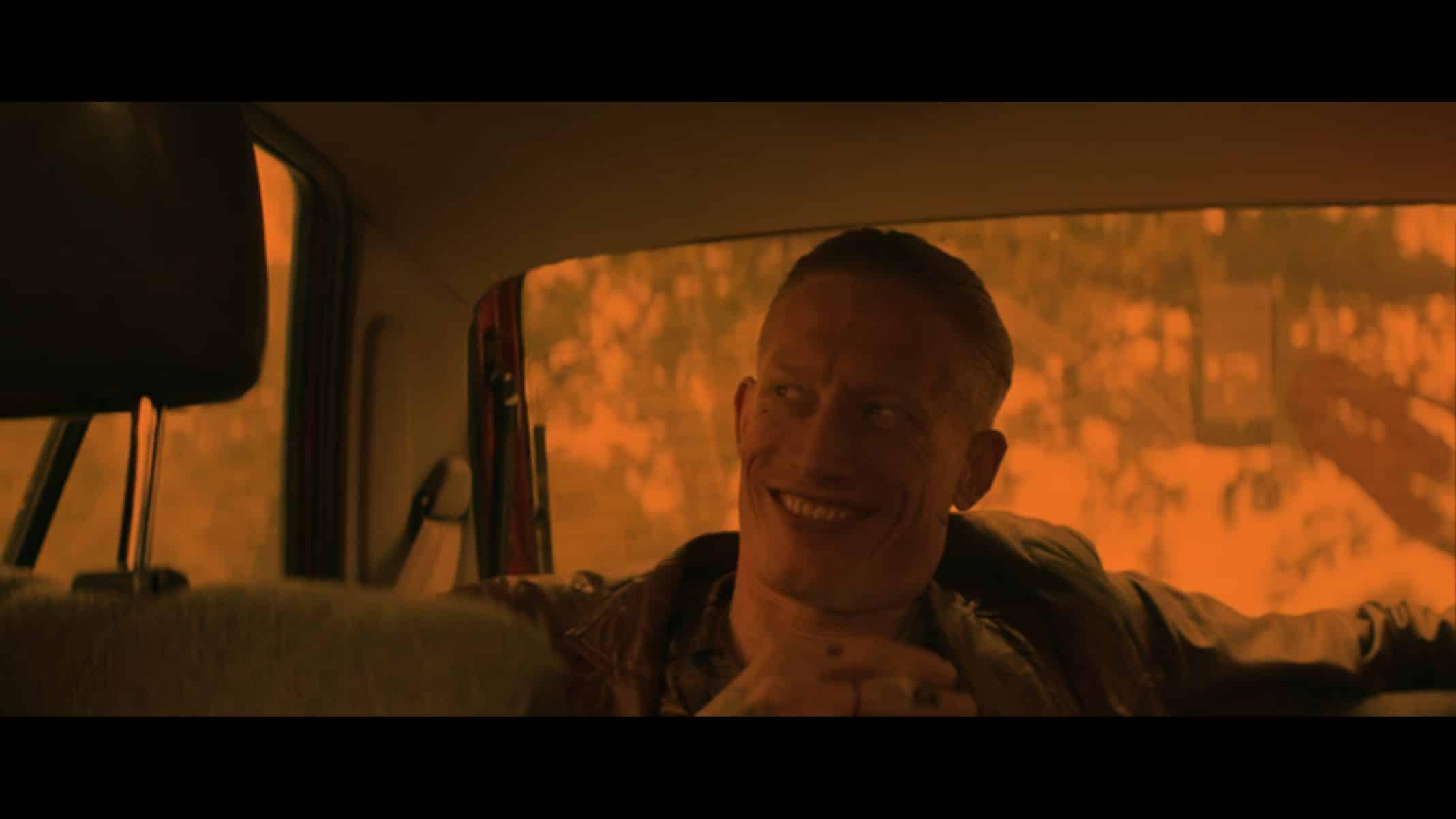 Gaz (Jake Curran) laughing in the backseat.