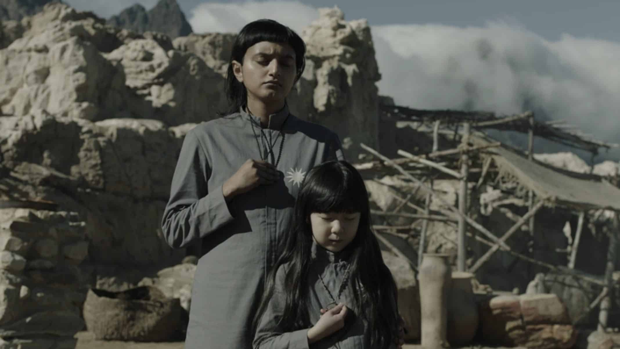Holly (Aasiya Shah) and Vita (Ivy Wong) praying