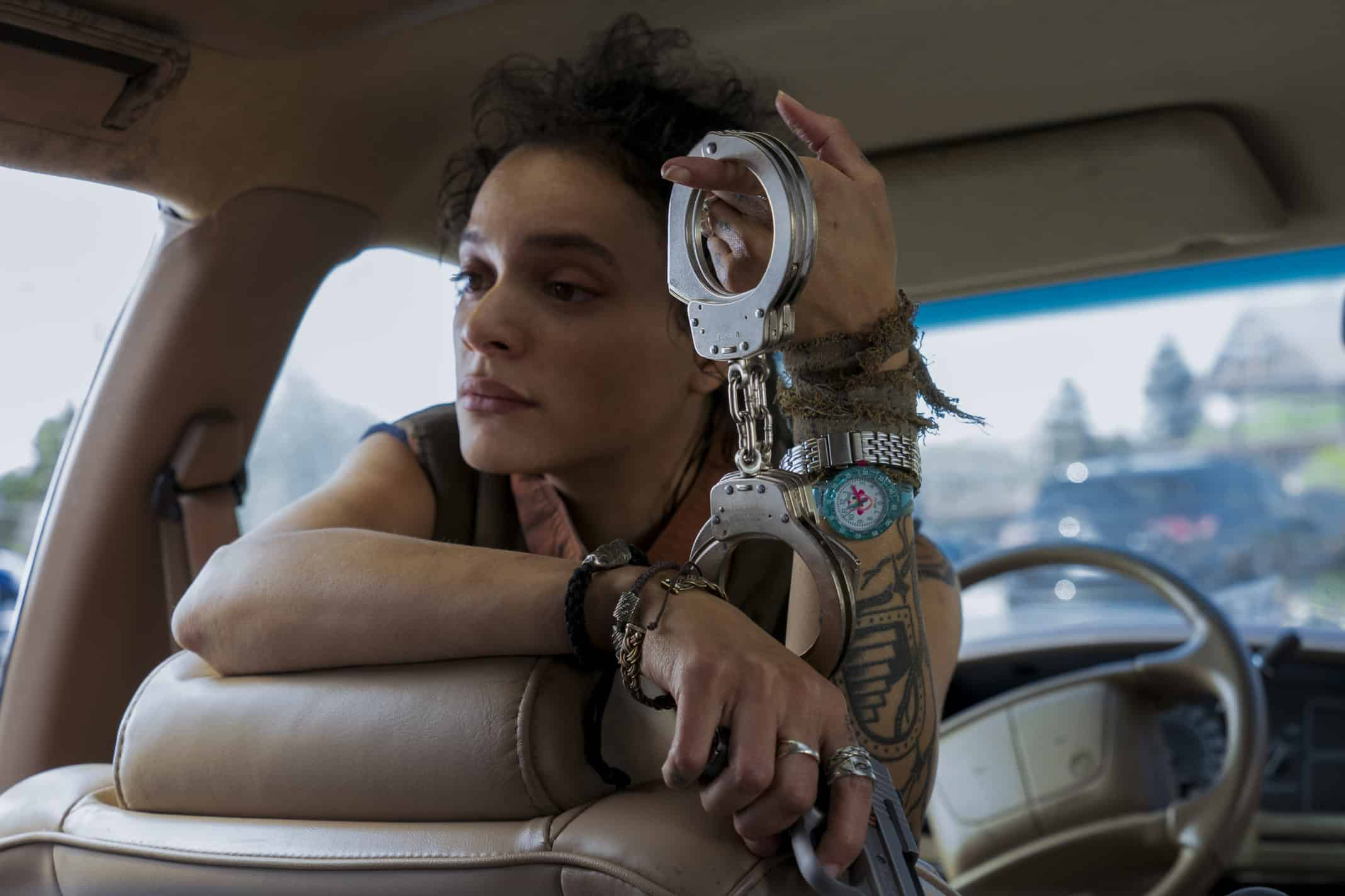 Jessica Hyde (Sasha Lane) with handcuffs in one hand and a gun in another.