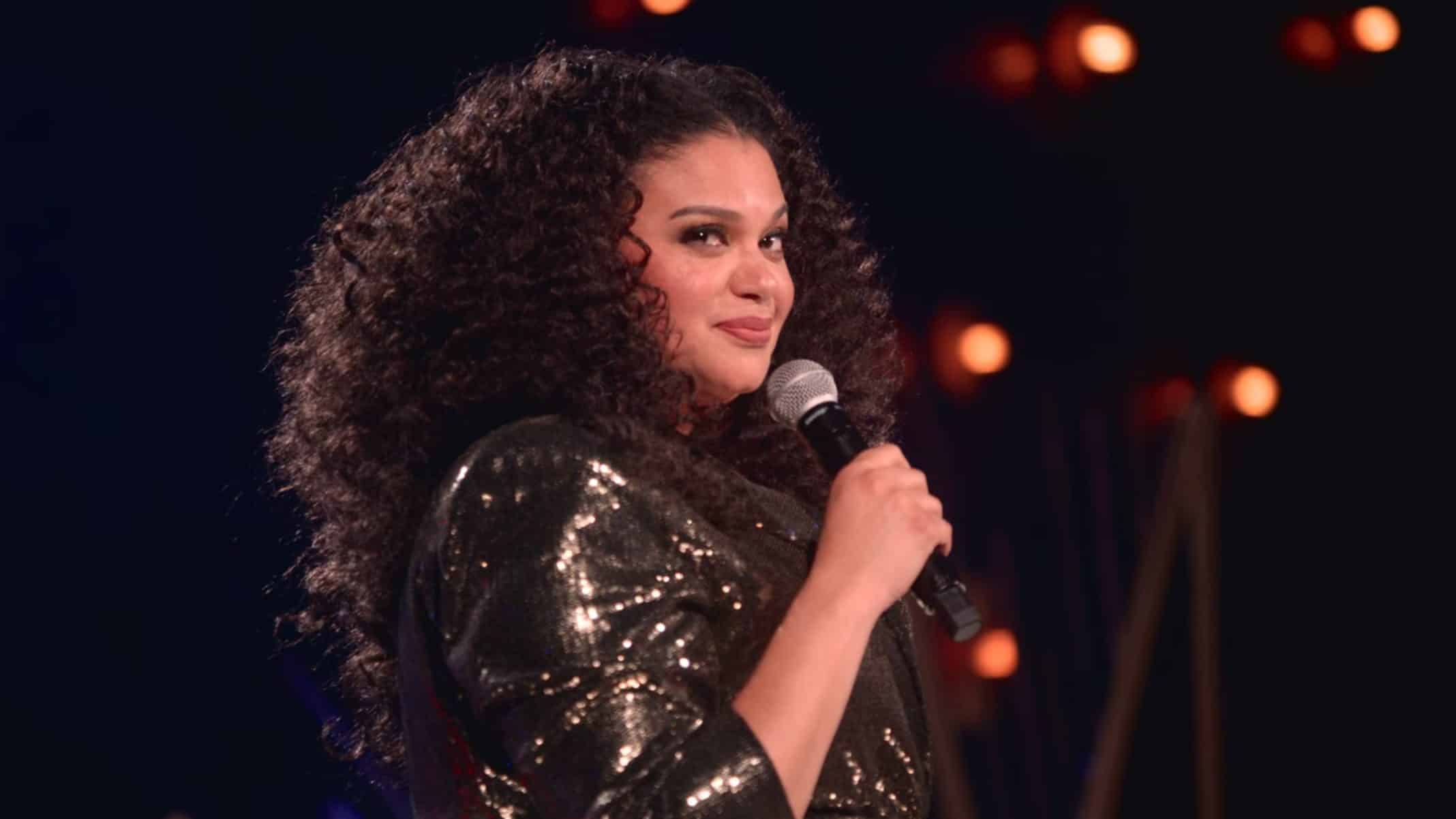 Michelle Buteau looking off to the side.