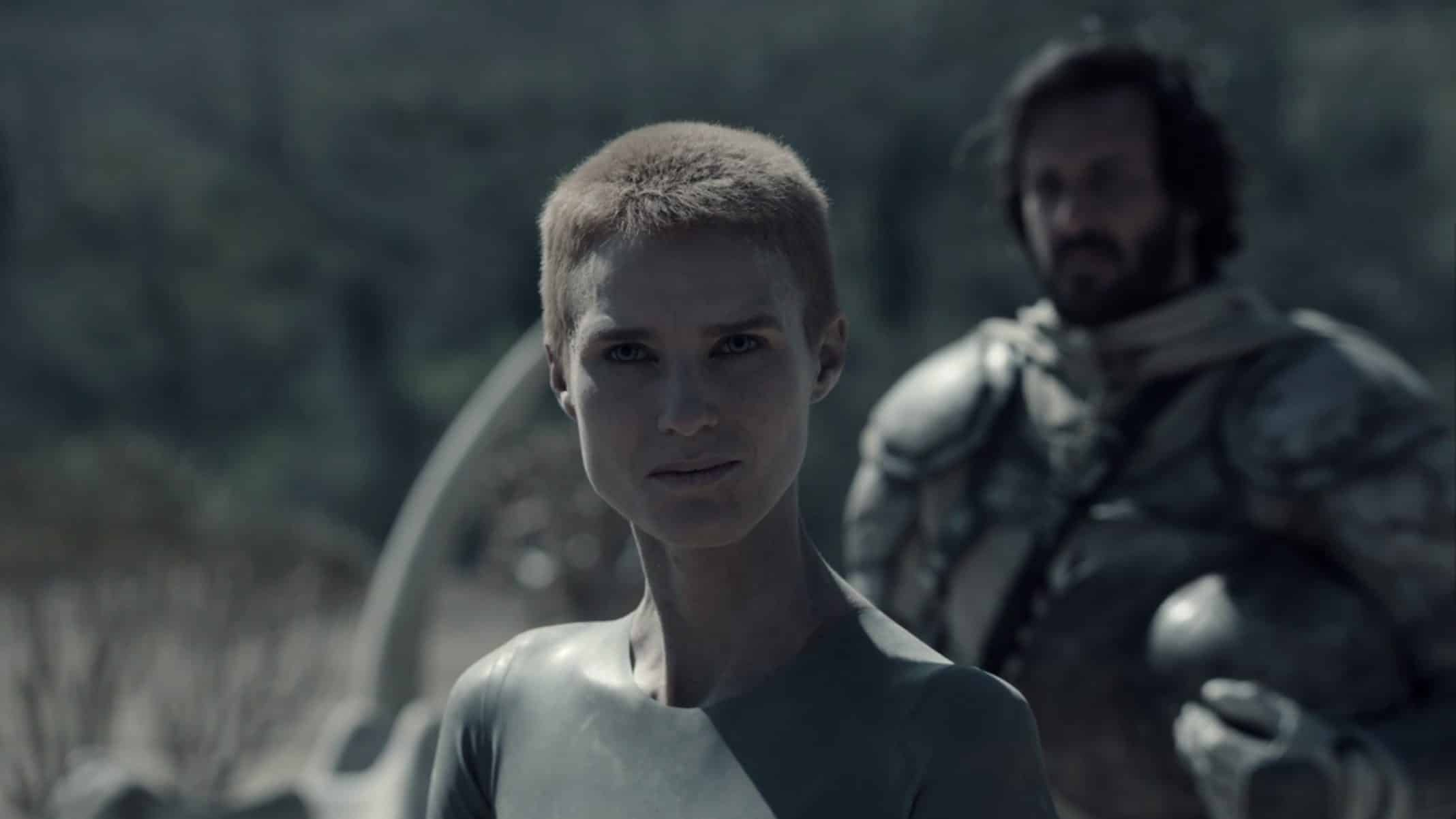 Mother (Amanda Collin) with a soldier behind her.