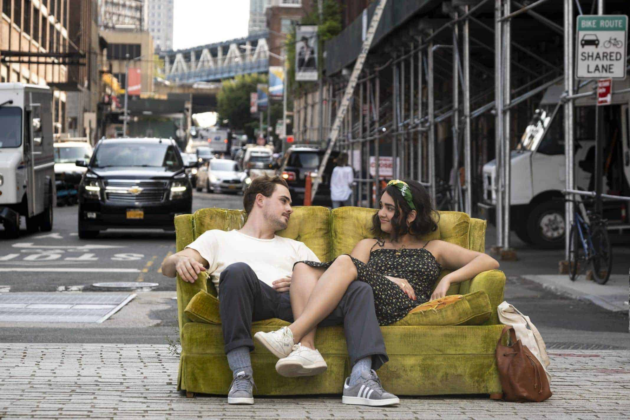 Nick (Dacre Montgomery) and Lucy (Geraldine Viswanathan) sitting on a couch together, outside.
