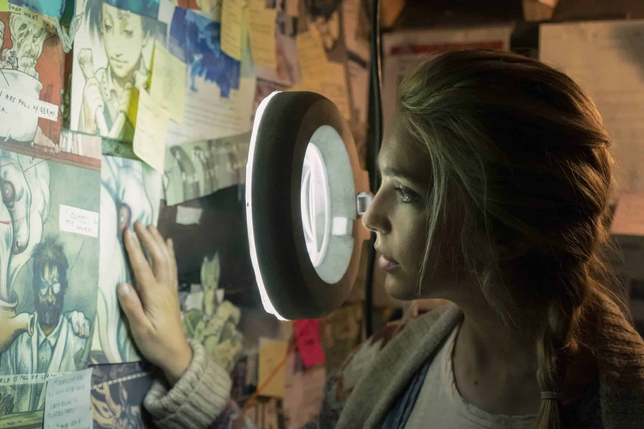 Samantha (Jessica Rothe) looking at Wilson Wilson's Utopia comics spread across the wall.