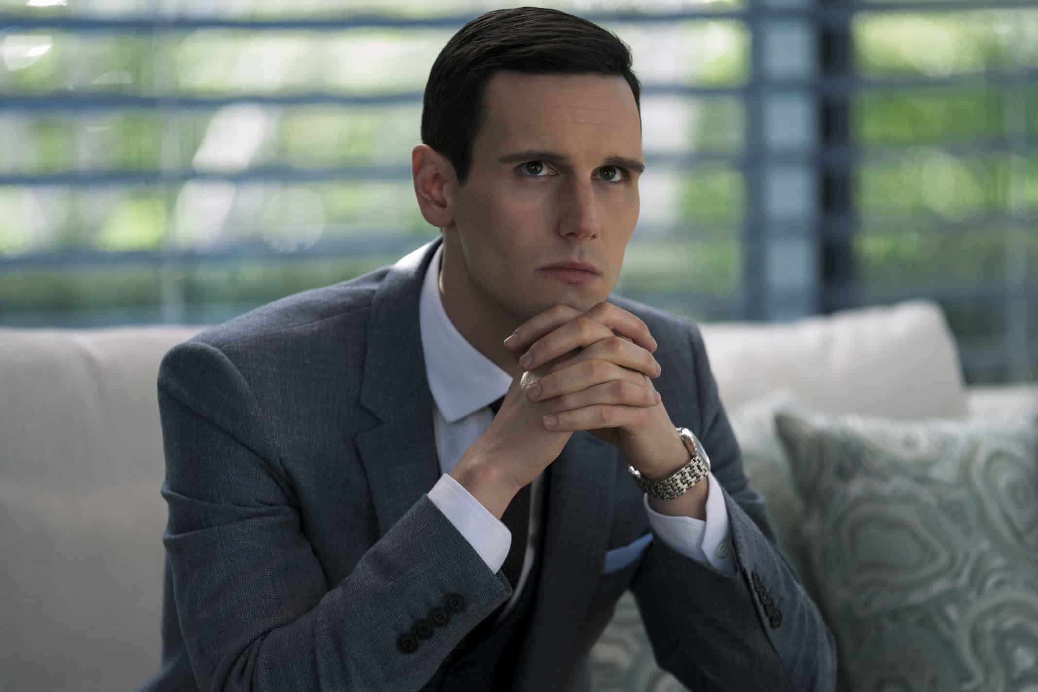 Thomas Christie (Cory Michael Smith) sitting in a corporate office.