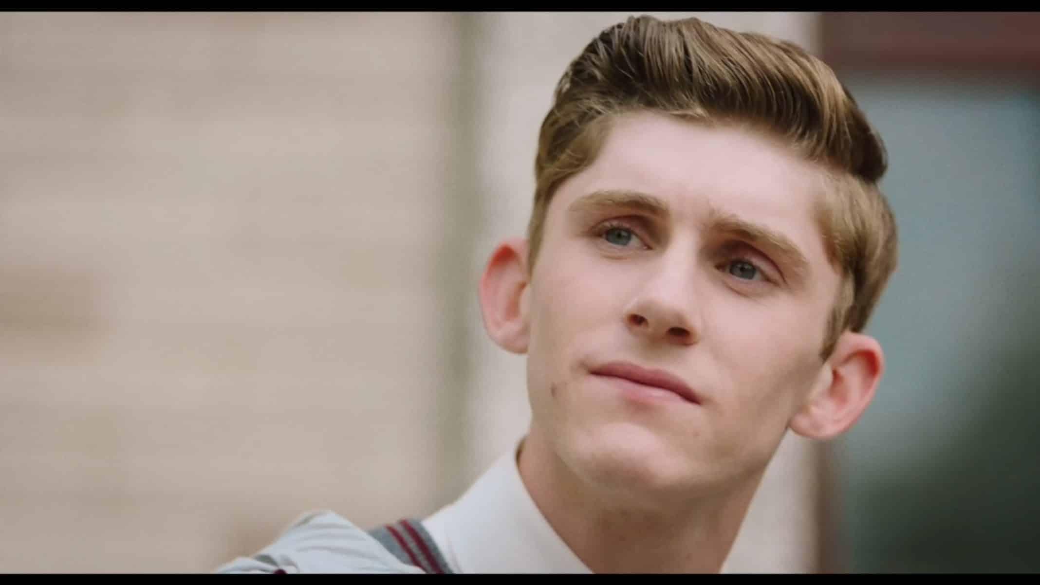 Eddie (Fionn O'Shea) sitting on stairs at school
