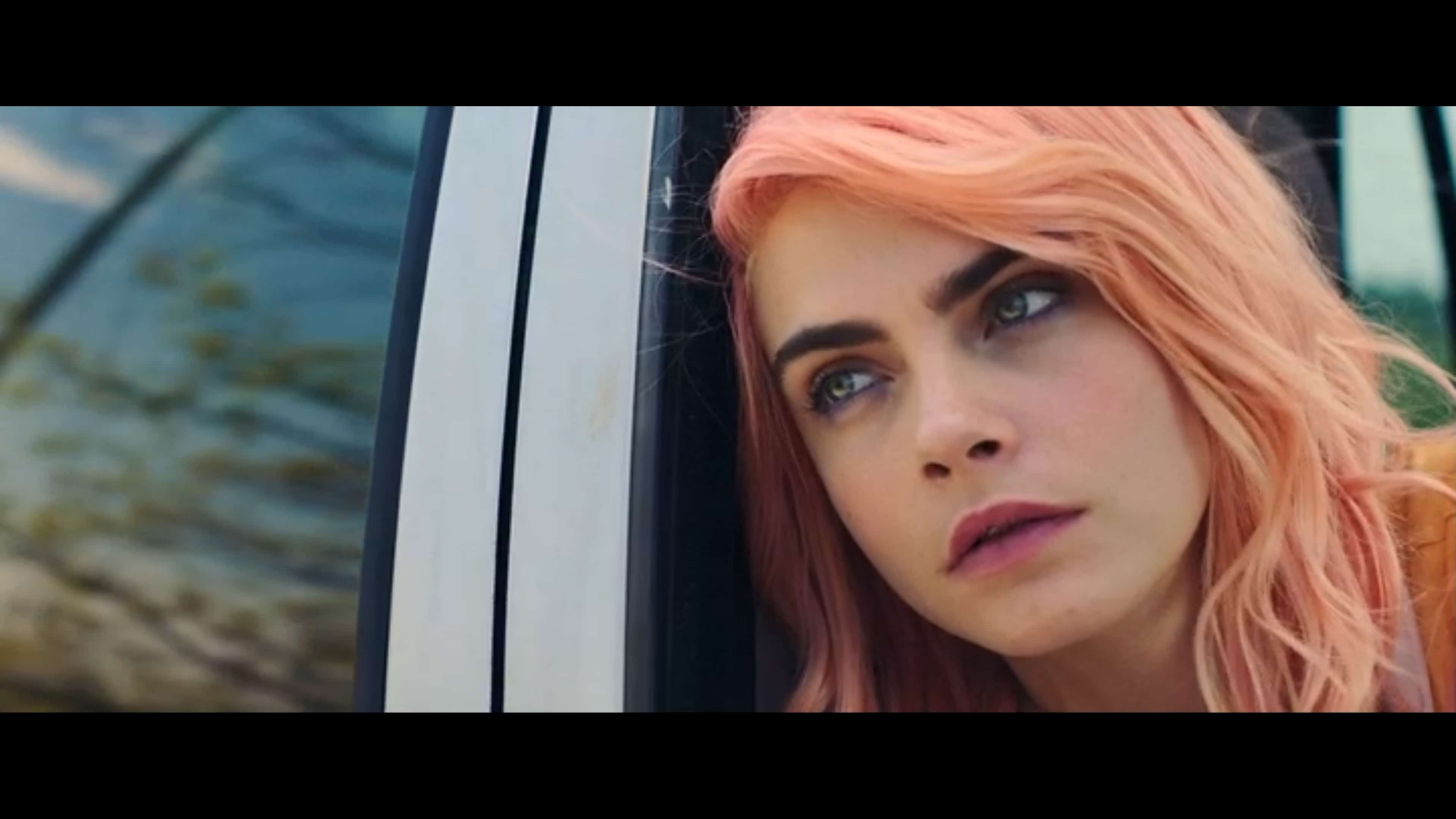 Isabelle (Cara Delevingne) looking out a window