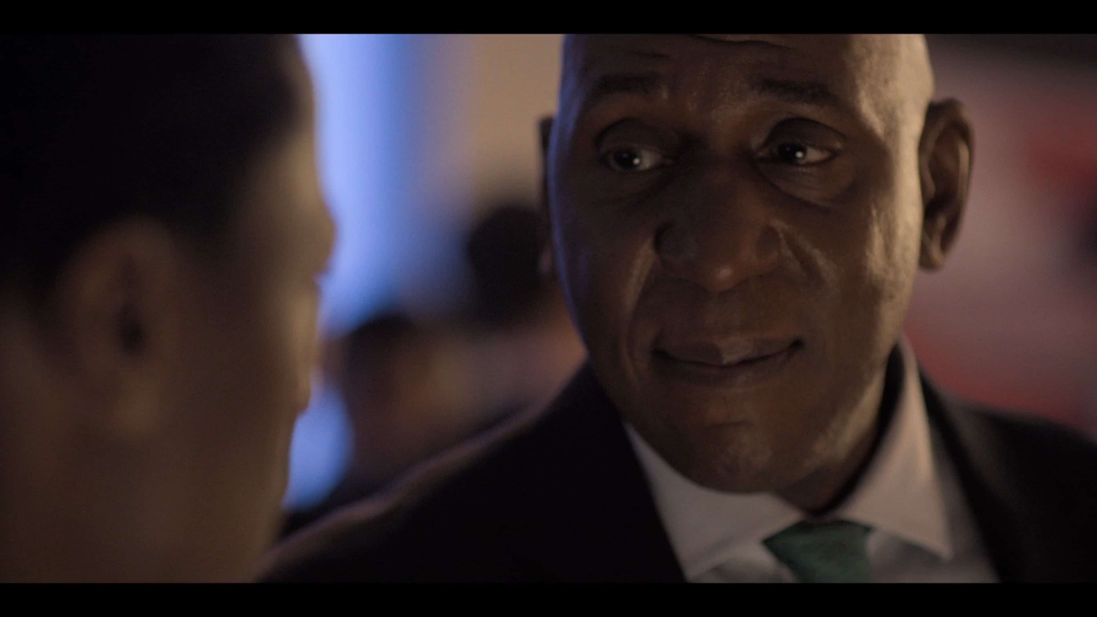 Lord Oki (Colin McFarlane) talking to Gus