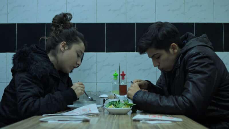 Emre (Lorin Merhart) and Nazli (Deniz Altan) having a meal together