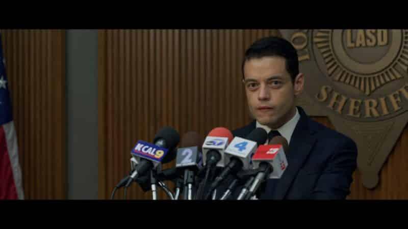 Jim (Rami Malek) holding a press conference