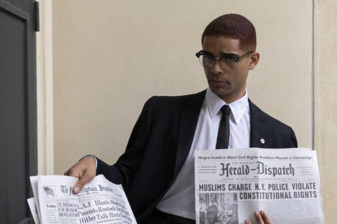 Malcolm X (Kingsley Ben-Adir) holding up a newspaper