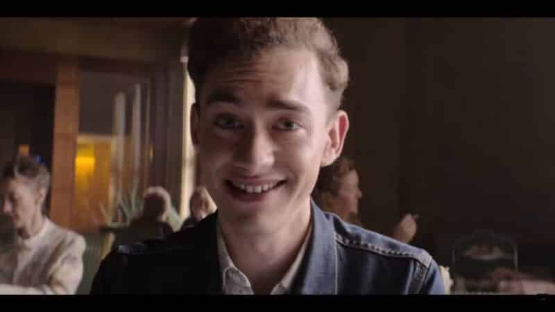 Ritchie (Olly Alexander) smiling and talking to a potential agent