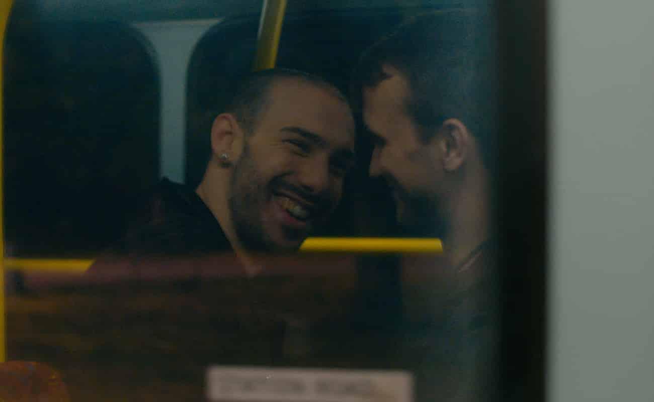 Sean (Aaron Cini) and Bryn (Richard Hay) talking on the bus