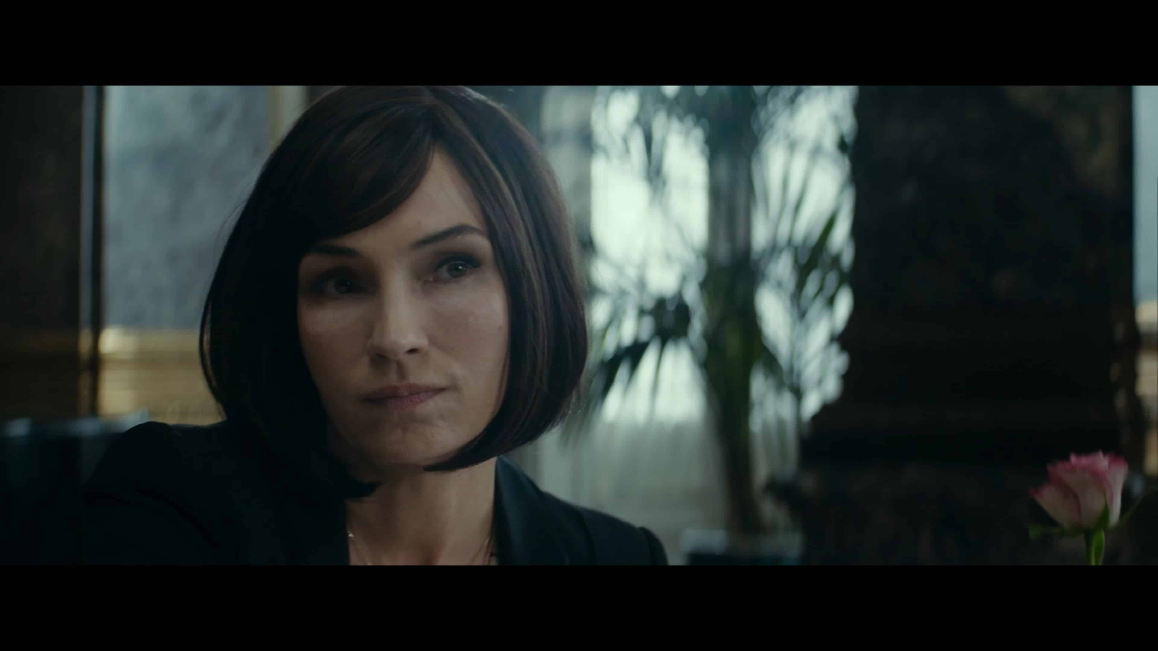 Margaret (Famke Janssen) talking with Walter, who is trying to commission a new deal with her