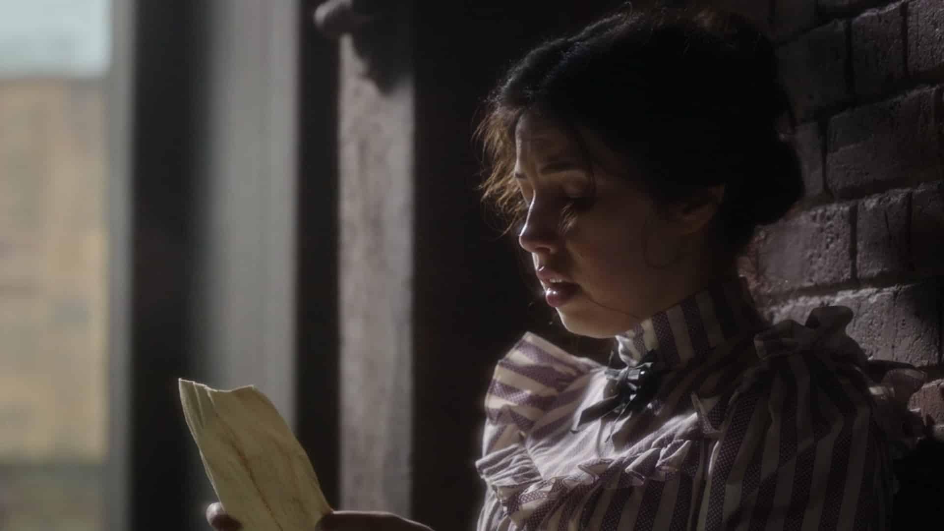 Beth (Ella Smith) reading a poster advertising Amalia's help