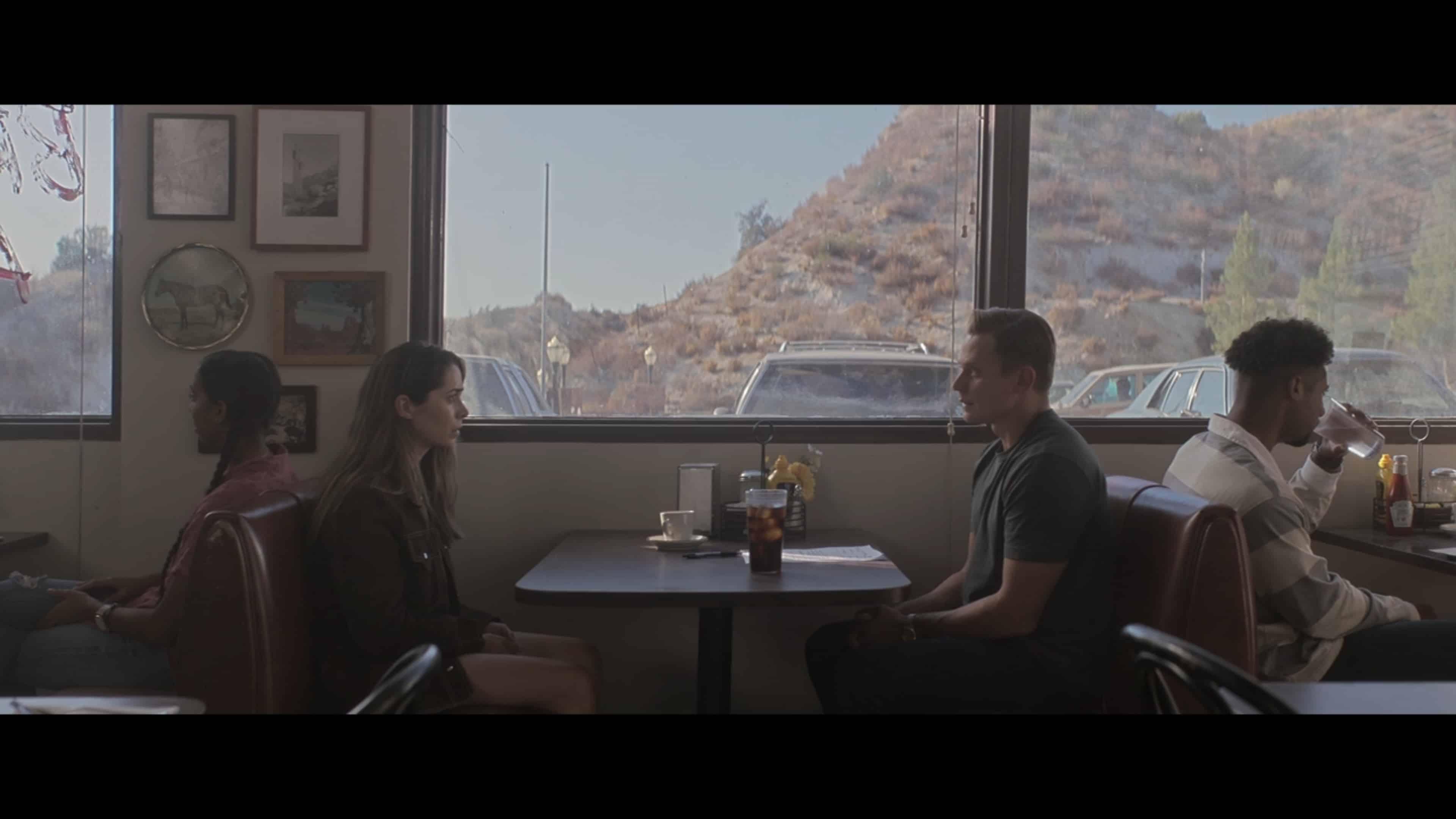 Hazel and Byron sitting at a diner together