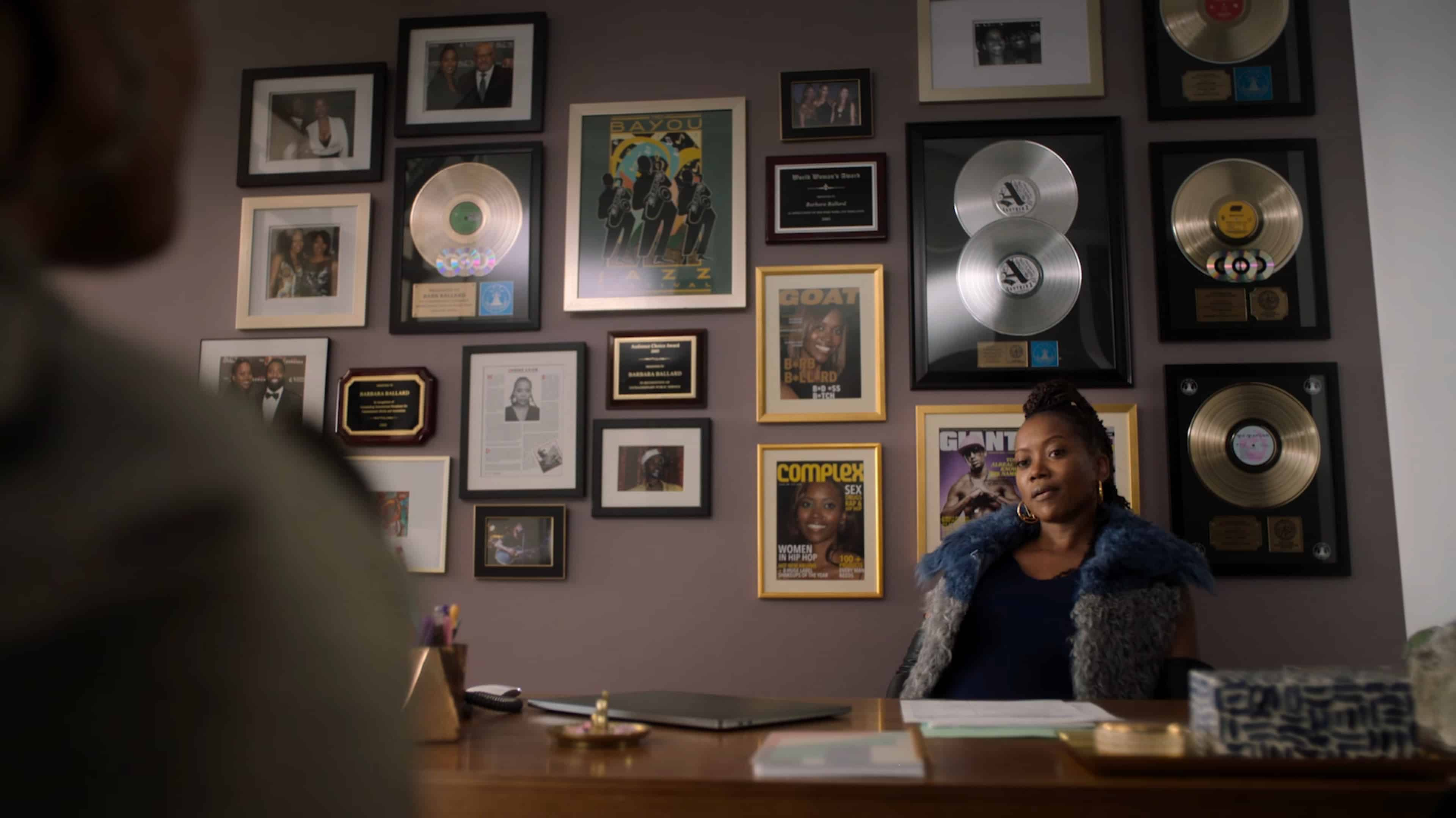 Barb (Erika Alexander) in her office with plaques and covers featuring her