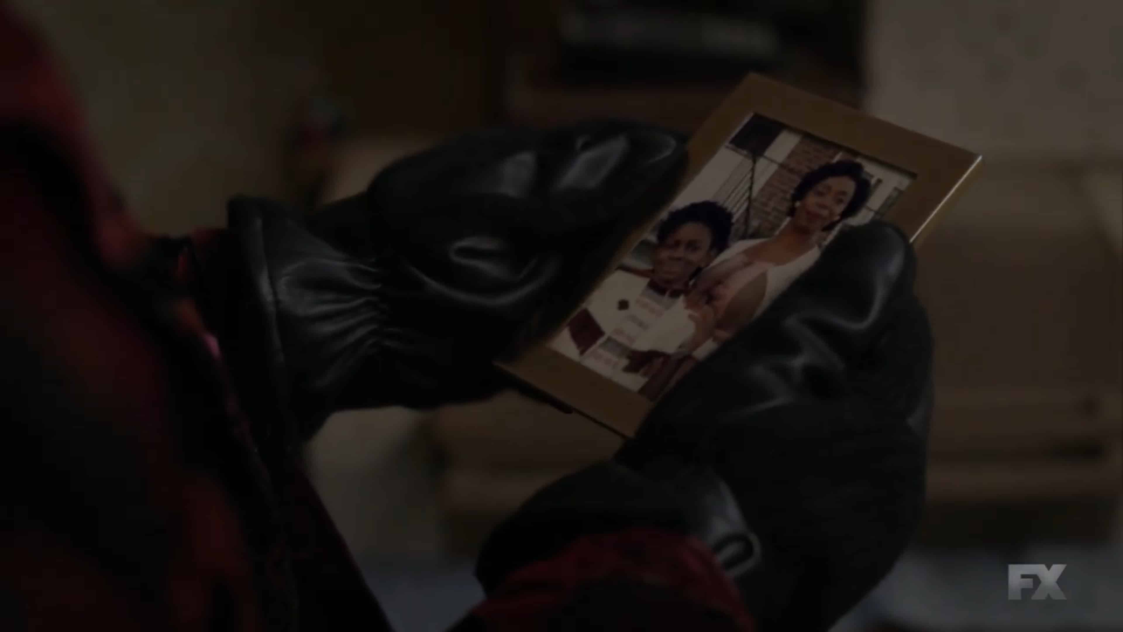Elektra looking at a younger picture of herself with her mom