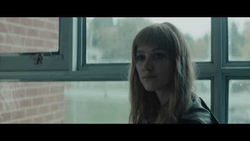 Cindy (Maika Monroe) in school, looking at Fred in the distance