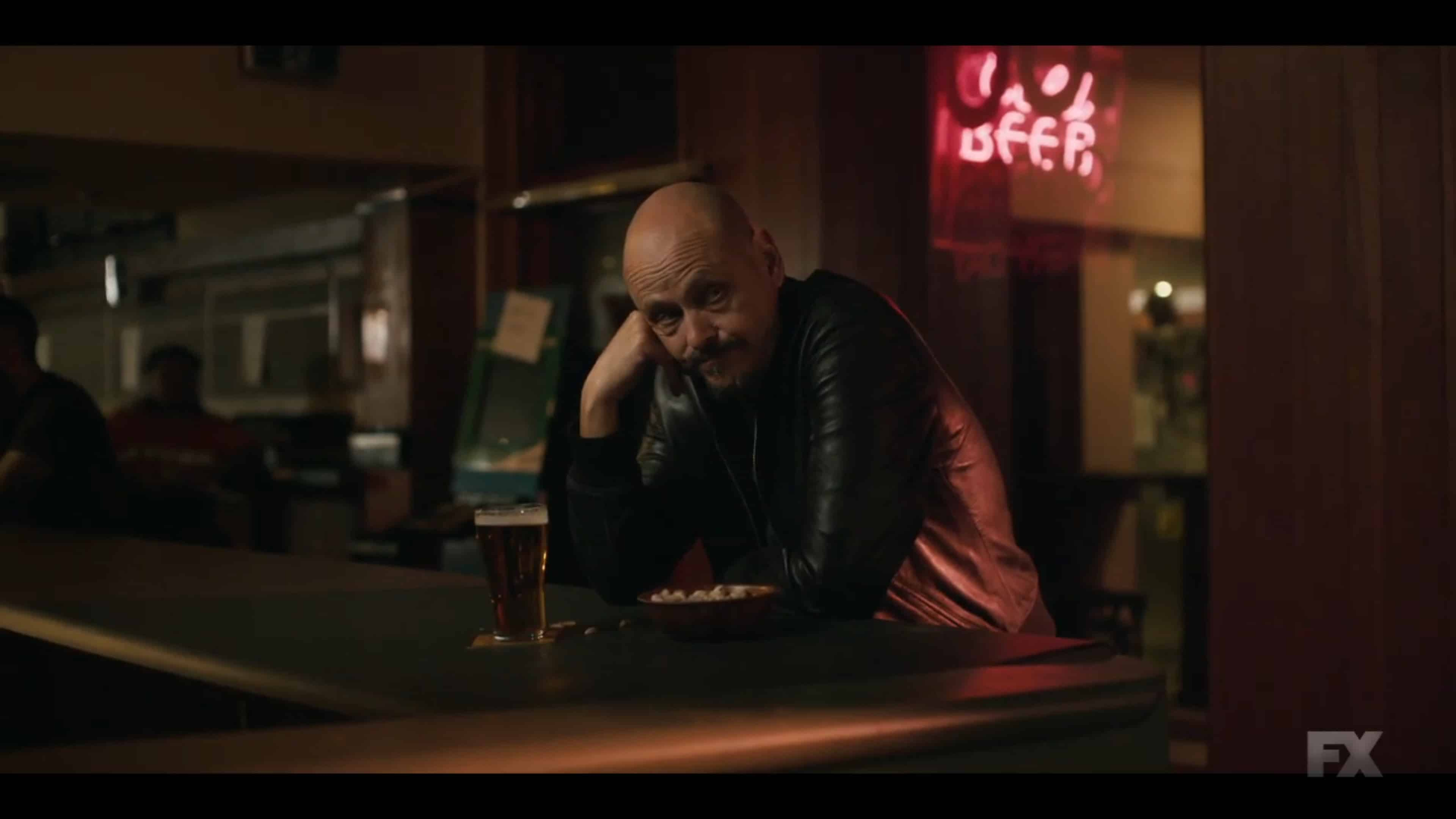 Ray sitting at a bar, watching people have fun