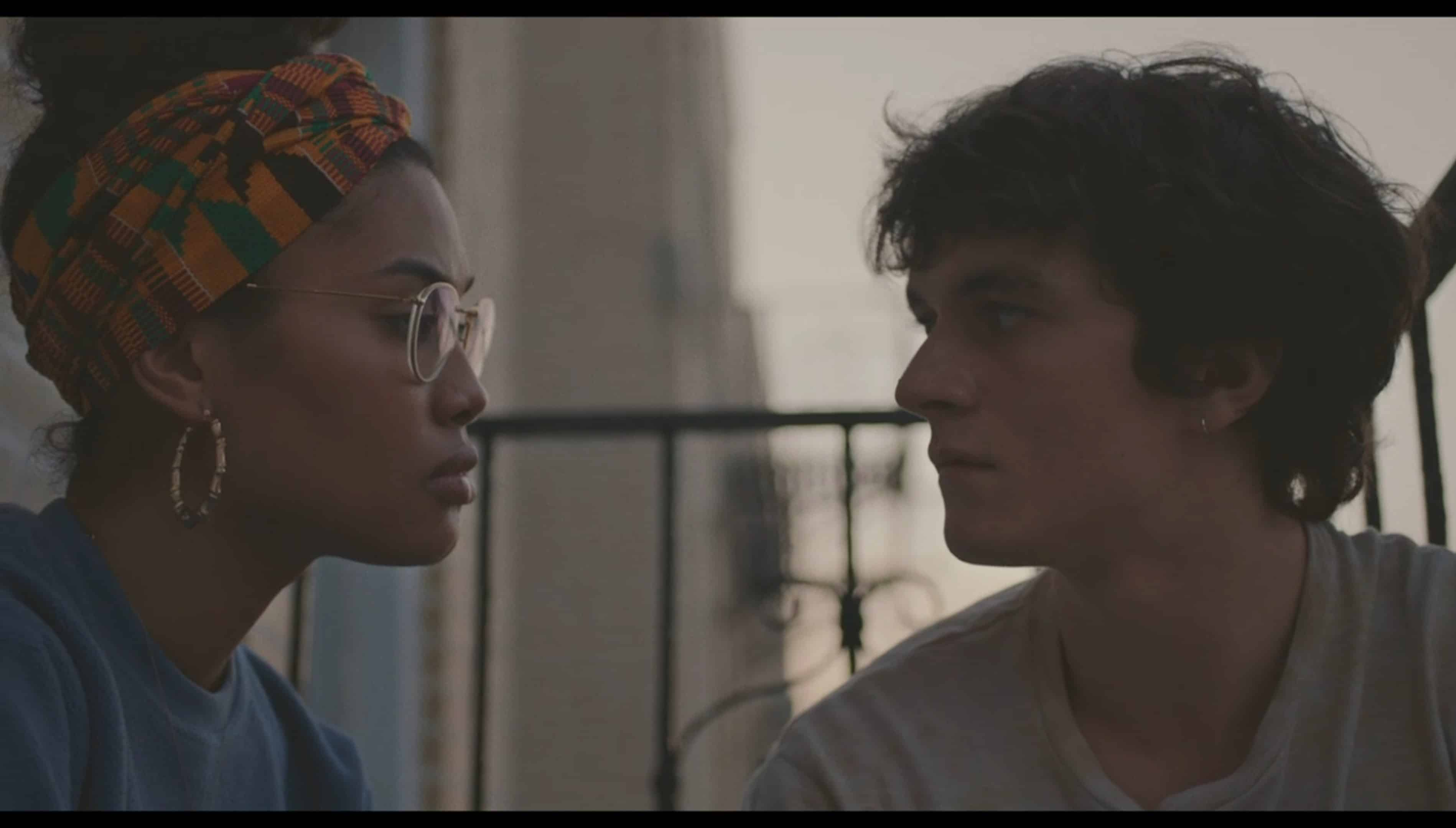Wye (Leyna Bloom) and Paul (Fionn Whitehead) chilling outside her window