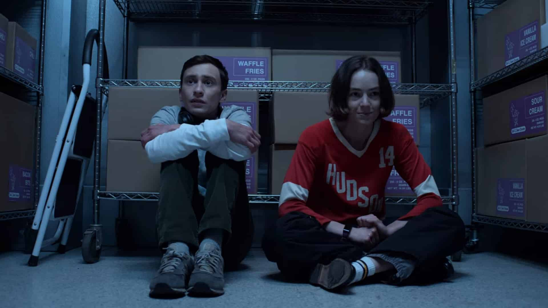 Sam and Casey sitting in a walk in freezer together
