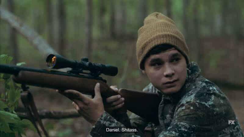 Daniel (Dalton Cramer) with a rifle in hand