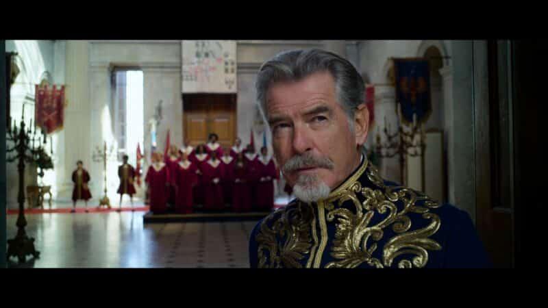 King Rowan (Pierce Brosnan) with a choir behind him